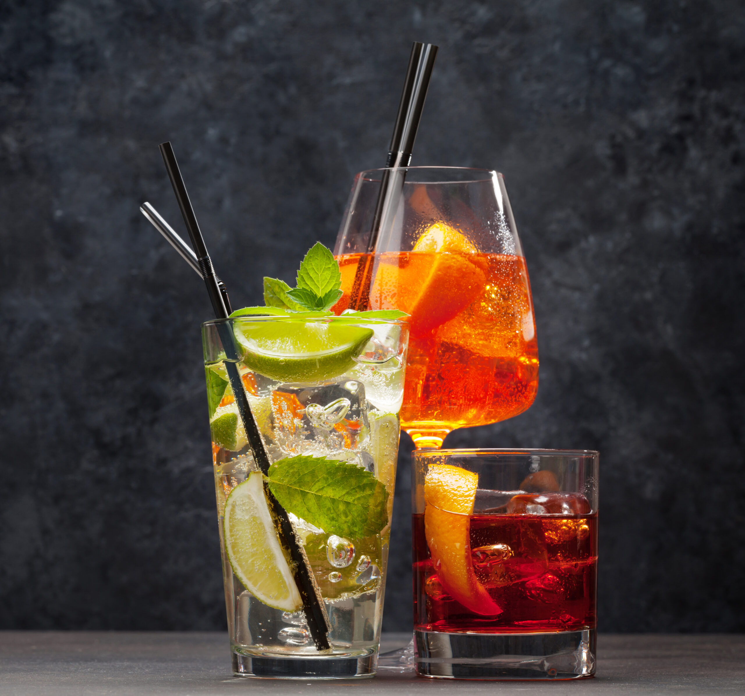 Three classic cocktail glasses on wooden table. Negroni, aperol spritz and mojito. With copy space
